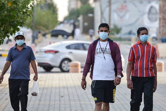 Mask-clad men walk along the promenade of Tahlia street in the centre of Riyadh