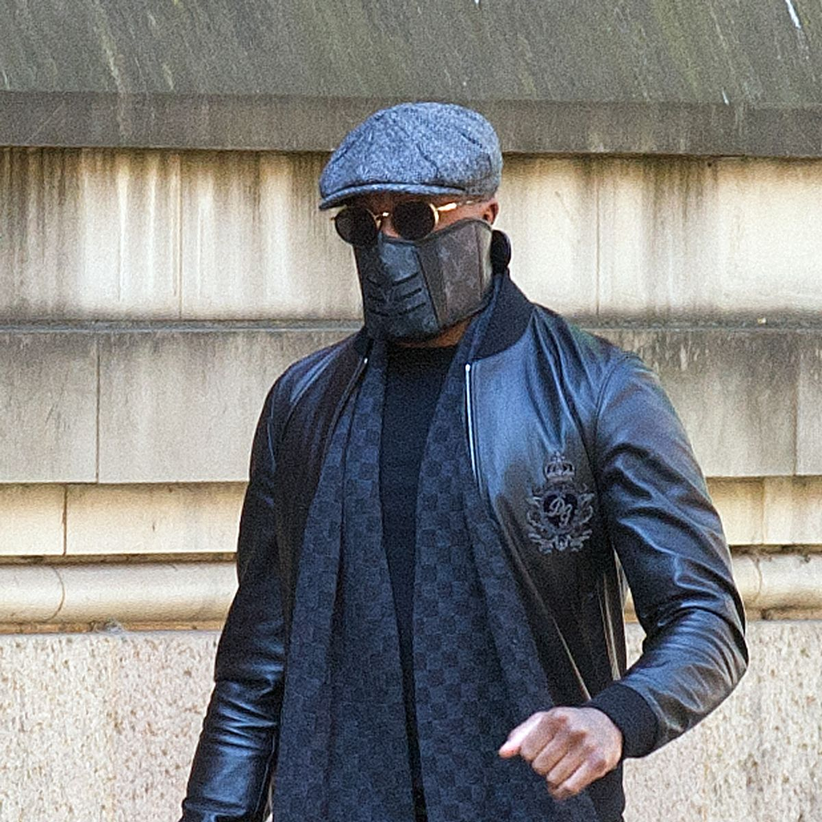 The musician - real name Aaron Davis - wore a black leather jacket, flat cap, a mask and sunglasses as he entered Minshull Street Crown Court on Monday morning