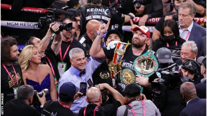 Tyson Fury defeats Deontay Wilder and celebrates in the ring with his belt and his entourage