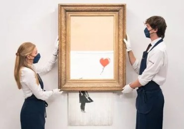 'Legendary piece!' Banksy's shredded Girl With Balloon sells at auction for £18.6m